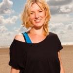 Happy pretty blond woman on the beach. Enjoying nature. Blue cloudy sky. Wearing black sweater. — Stock Photo
