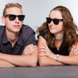 Happy young couple with black sunglasses casual dressed. Studio shot isolated on grey background. Man with short blond hair. Woman long brown hair. — Stock Photo