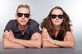 счастливый молодая пара с черные очки случайные одет. студия выстрел изолированные на сером фоне. человек с короткими светлыми волосами. женщина длинные каштановые волосы. — Стоковое фото