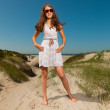 Happy pretty girl with long brown hair enjoying sand dunes near the beach on hot summers day. Wearing singlasses. Clear blue sky. — Stock Photo #11997886