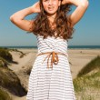 Happy pretty girl with long brown hair enjoying sand dunes near the beach on hot summers day. Clear blue sky. — Stock Photo