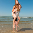 Two pretty girls playing and enjoying the refreshing on a hot summers day. Clear blue sky. Having fun on the beach. — Stock Photo #11998074