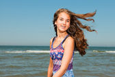 Happy pretty girl with long brown hair enjoying the refreshing beach on hot summers day. Clear blue sky. — Stock Photo