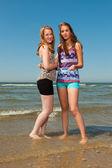 Twee mooie meisjes spelen en genieten van de verfrissende op een hete zomers dag. duidelijke blauwe hemel. plezier op het strand. — Stockfoto