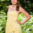 Pretty young woman with long brown hair enjoying nature in forest. Blurred green background. Wearing yellow dress. — Stock Photo #12015957