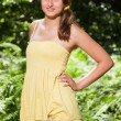 Pretty young woman with long brown hair enjoying nature in forest. Blurred green background. Wearing yellow dress. — Stock Photo