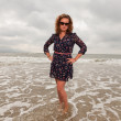 Pretty young woman enjoying outdoor nature near the beach. Standing in the water. Red hair. Wearing dark blue dress and black sunglasses. Cloudy sky. — Stock Photo