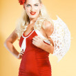 Sexy blonde pin up girl wearing red swimwear holding a little suitcase and white umbrella. Retro style. Fashion studio shot isolated on yellow background. — Stock Photo