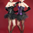 Two burlesque pin up women with black hair dressed in purple and black. Sexy pose. Wearing black hat. Studio fashion shot isolated on red background. — Stock Photo #12194972