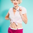Sexy blonde pin up girl wearing pink shirt and hot pants holding sunglasses. Retro style. Fashion studio shot isolated on light blue background. — Stock Photo