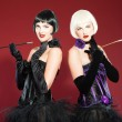 Royalty-Free Stock Photo: Two burlesque pin up women with black hair dressed in purple and black. Sexy pose. Wearing black hat. Studio fashion shot isolated on red background.
