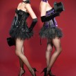 Two burlesque pin up women with black hair dressed in purple and black. Sexy pose. Wearing black hat. Studio fashion shot isolated on red background. — Stock Photo #12195014