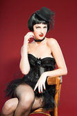 Burlesque pin up woman with black hair dressed in black. Sexy pose. Sitting on chair. Wearing black hat. Studio fashion shot isolated on red background. — Stock Photo