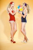 Deux sexy blonde pin-up jeunes filles portant des maillots de bain bleu et rouge, tenant un ballon de plage coloré. style rétro. studio mode tir isolé sur fond jaune. — Photo