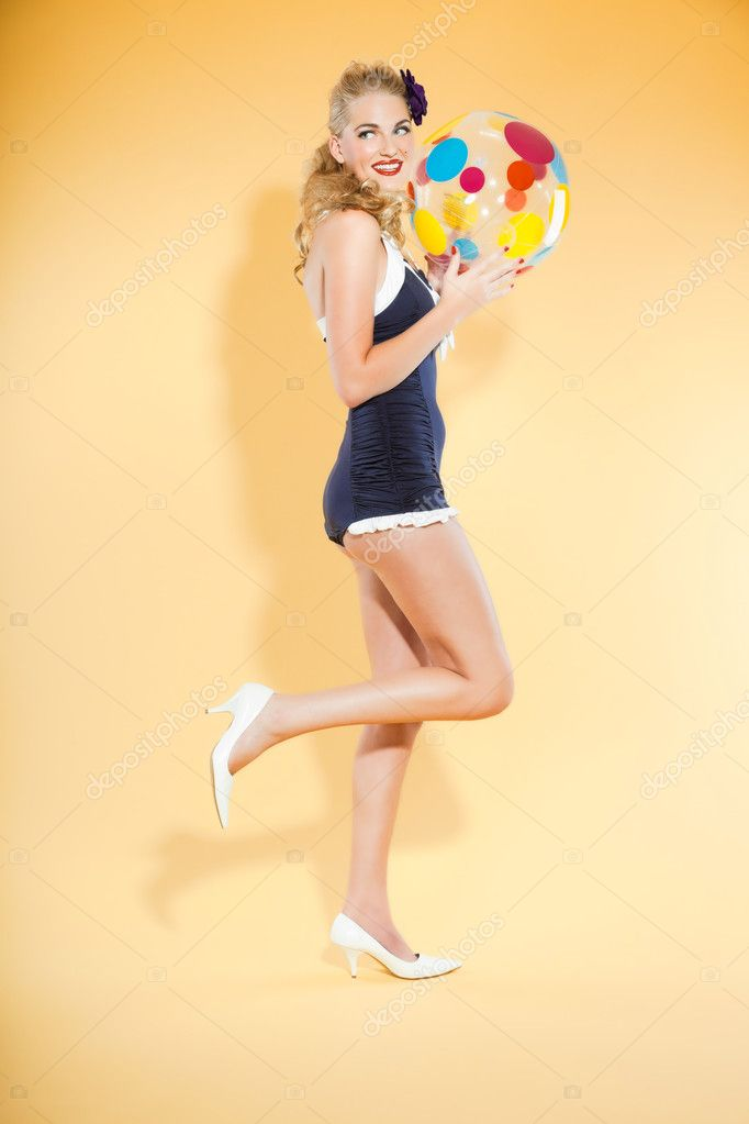 Sexy blond pin up girl wearing blue swimwear holding a colorful beach ball. Retro style. Fashion studio shot isolated on yellow background. — Stock Photo #12194920