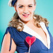 Sexy blonde pin up girl wearing blue dress with white dots and marine cap. Holding pink lollypop. Retro style. Fashion studio shot isolated on light blue background. — Stock Photo #12362256