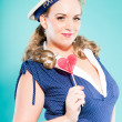 Sexy blonde pin up girl wearing blue dress with white dots and marine cap. Holding pink lollypop. Retro style. Fashion studio shot isolated on light blue background. — 图库照片