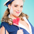 Sexy blonde pin up girl wearing blue dress with white dots and marine cap. Holding pink lollypop. Retro style. Fashion studio shot isolated on light blue background. — Stock Photo