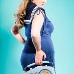 Sexy blonde pin up girl wearing blue dress with white dots and marine cap. Holding vintage radio. Retro style. Fashion studio shot isolated on light blue background. — Stock Photo #12362327