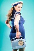 Sexy blonde pin up girl wearing blue dress with white dots and marine cap. Holding vintage radio. Retro style. Fashion studio shot isolated on light blue background. — Stock Photo