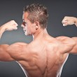Shirtless muscled fitness man showing his back. Cool looking. Tough guy. Blue eyes. Blond short hair. Wearing black sunglasses. Tanned skin. Studio shot isolated on grey background. — Stock Photo #12389264