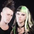 Stock Photo: Couple of cyber punk girl with green blond hair and punk man with mohawk haircut. Isolated on black background. Studio shot.