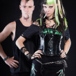 Couple of cyber punk girl with green blond hair and punk man with mohawk haircut. Expressive faces. Smoking cigarette. Isolated on black background. Studio shot. — Stock Photo