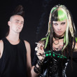 Couple of cyber punk girl with green blond hair and punk man with mohawk haircut. Expressive faces. Smoking cigarette. Isolated on black background. Studio shot. — Stock Photo #12402882