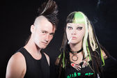 Couple of cyber punk girl with green blond hair and punk man with mohawk haircut. Isolated on black background. Studio shot. — Stockfoto