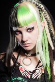 Cyber punk girl with green blond hair and red eyes isolated on black background. Expressive face. Studio shot. — Stockfoto