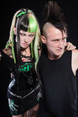 Couple of cyber punk girl with green blond hair and punk man with mohawk haircut. Expressive faces. Isolated on black background. Studio shot. — Foto Stock