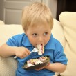 Adorable boy eating cake in a chair with a fork — Stock Photo #11063499