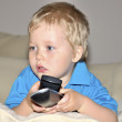 Cute kid watching tv, sitting in a very comfortable and soft cha — Stock Photo #11063740