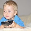 Cute kid watching tv, sitting in a very comfortable and soft cha — Stock Photo #11063758