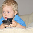 Cute kid watching tv, sitting in a very comfortable and soft cha — Stock Photo #11063771