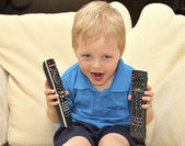 Cute kid watching tv, sitting in a very comfortable and soft cha — Stock Photo