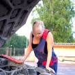 Beautiful woman repairing the car — Stock Photo