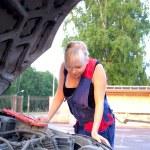 Beautiful woman repairing the car — Stock Photo