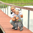 Father and son  on  a wooden pier near a river — Stock Photo