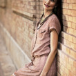 Beatiful woman leaning against a brick wall — Stock Photo