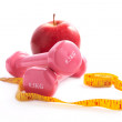 Apple and dumbbells  with a measuring tape. — Stock Photo