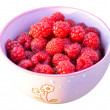 Raspberries fruit in a violet bowl, white background — Stock Photo