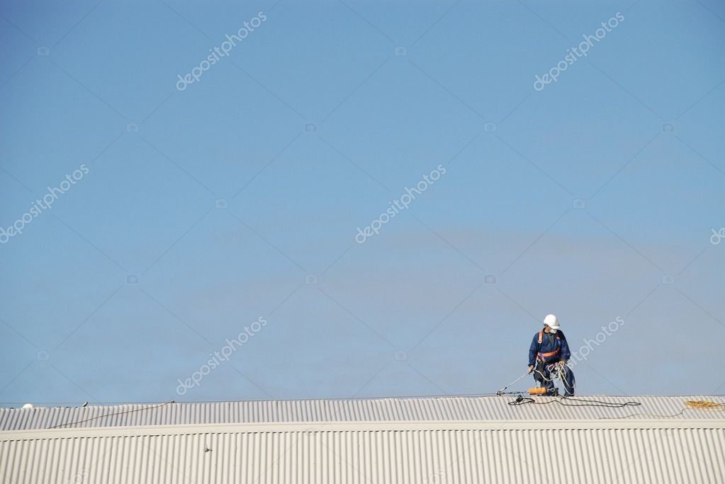 Man harnessed in working on a corrugated iron roof.  Stock Photo #10824890