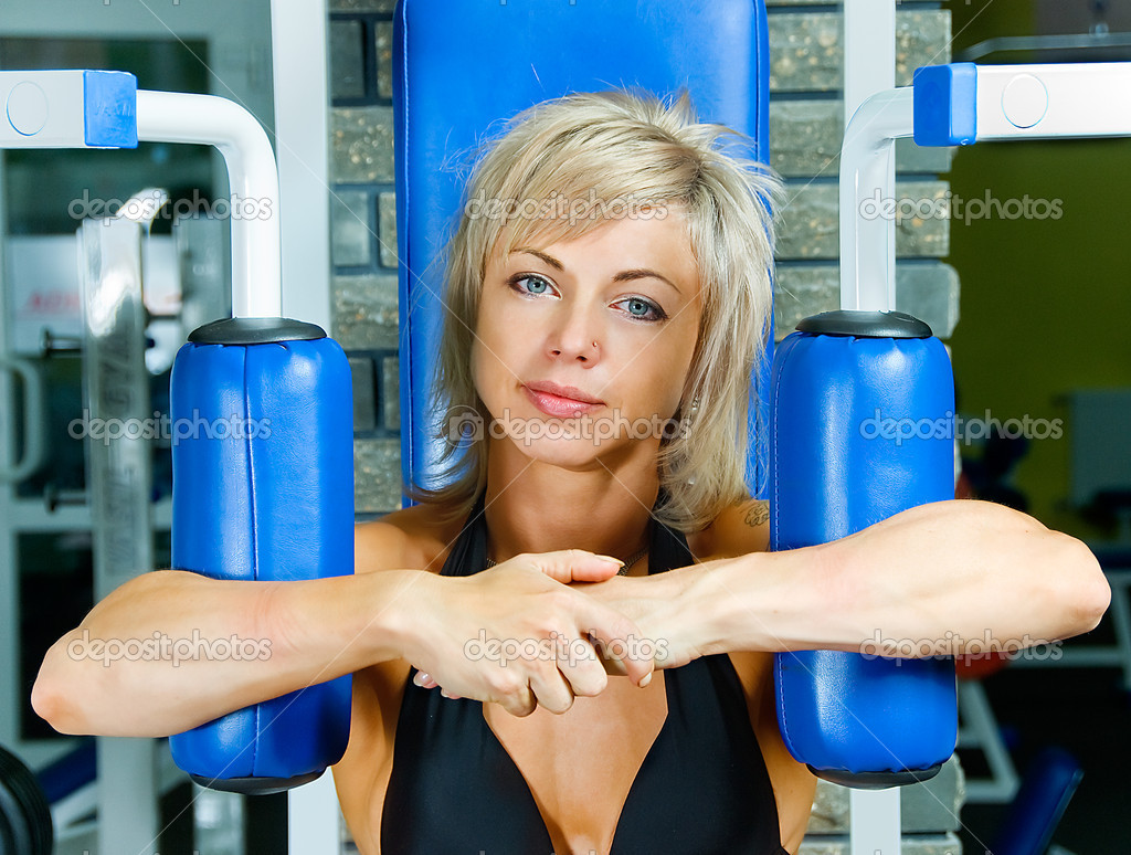 Young smiling woman bodybuilder in practice hall — Stock Photo #11347213