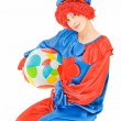 Young woman clown sitting on white background with a ball — Stock Photo #11502526