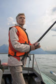 A fisherman wearing a life jacket. — Stock Photo