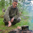 A man cooks sausages on the fire - Stock Photo