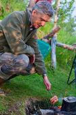 Un uomo cuoce salsicce sul fuoco — Foto Stock