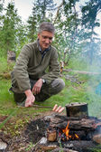 A man cooks sausages on the fire — Stock Photo