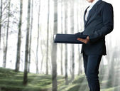 Young business man standing with a file — Stok fotoğraf
